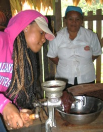 A student grinds cacao nibbs into a paste as part of the chocolate-making process.