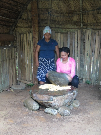 A student learns to grind corn into flour with a large stone.