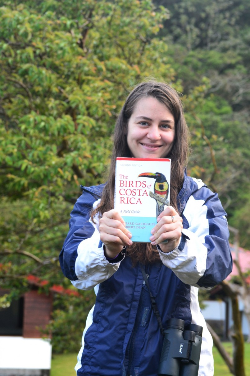 Resident naturalist Jessica Murray holds the Birds of Costa Rica book, a helpful reference for bird count day!