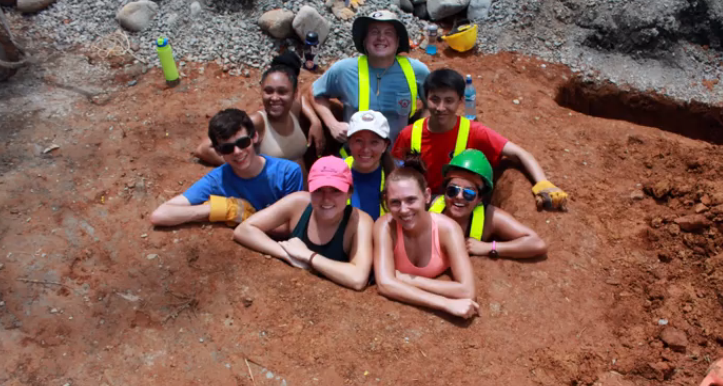 Students proudly pile into one of their completed holes.