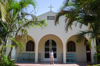 Joshua stands in front of the small church in San Luis.